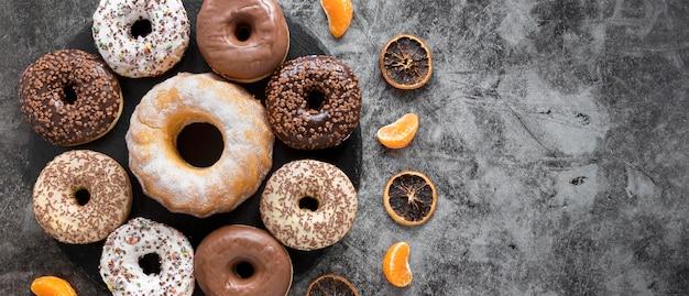 乾燥した柑橘類とコピースペースを持つさまざまなドーナツのフラットレイアウト