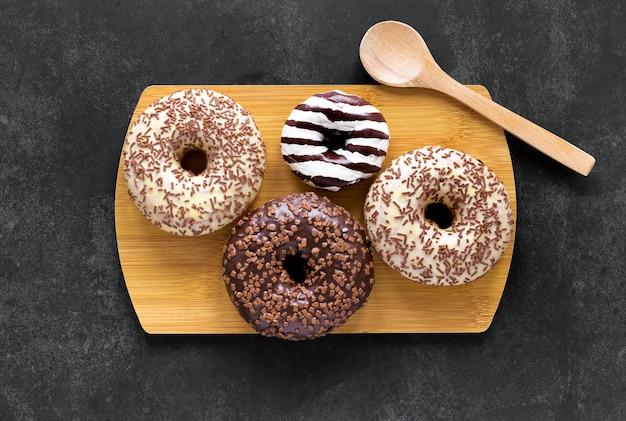 Плоская кладка пончиков на разделочную доску с деревянной ложкой