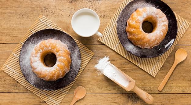 Плоская укладка пончиков на тарелки с деревянной ложкой и ложкой