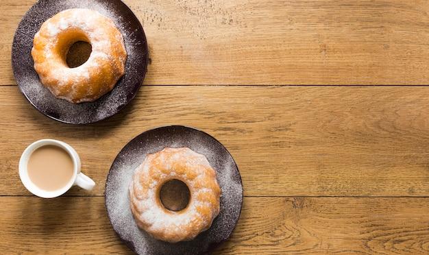 Плоская укладка пончиков на тарелках с кофе и копией пространства