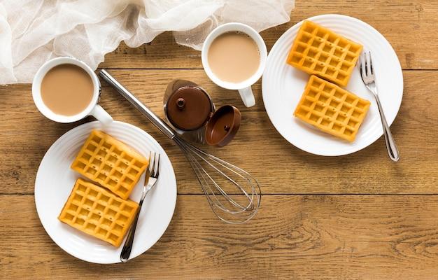 Плоские вафли на тарелках с венчиком и кофе