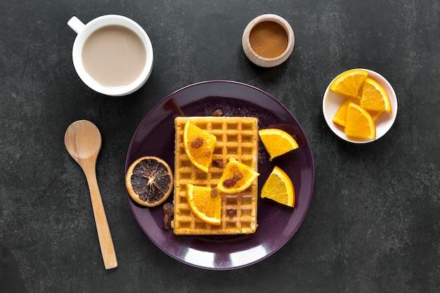 Плоские вафли на тарелке с цитрусовыми и кофе