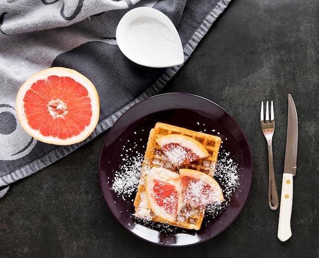 Вид сверху тарелки с вафлями и цитрусовыми пудрой с сахарной пудрой