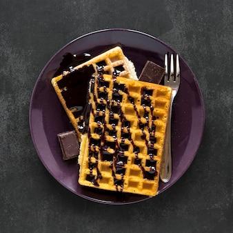 Вид сверху тарелки с вафлями и шоколадным соусом