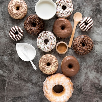 Вид сверху разнообразных пончиков с молоком и сахарной пудрой