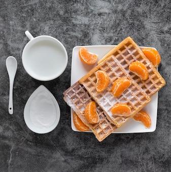 Вид сверху вафли с мандаринами и молоком
