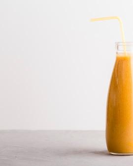 コピースペース付き正面オレンジ色のスムージーボトル