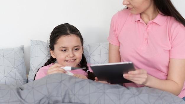 Крупным планом девушка в постели с планшетом