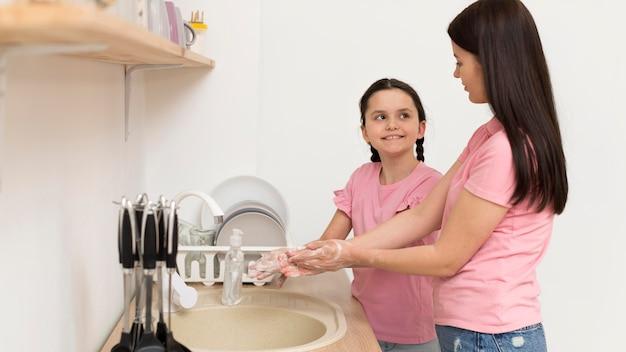 母と女の子の手を洗う