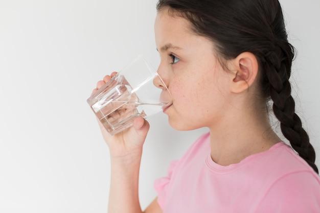 屋内で水を飲む女の子