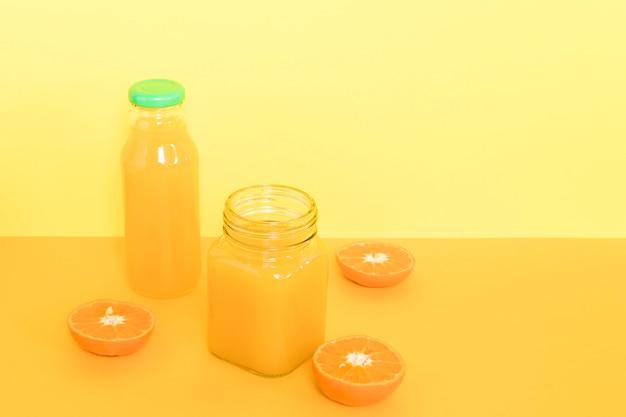 オレンジのスムージーとカップ