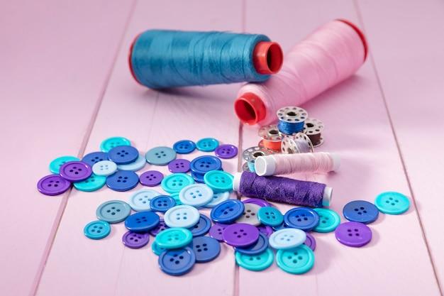 Большой угол кнопок с челноками швейных машин и катушками с нитками
