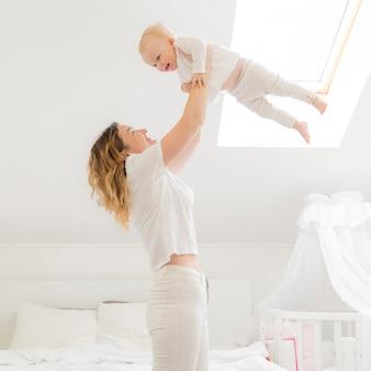 自宅でかわいい赤ちゃんと遊ぶ大人の母親