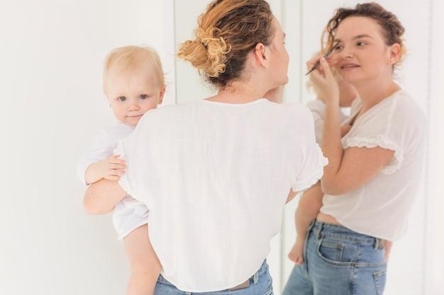 女の赤ちゃんを押しながら彼女の化粧をしている母親