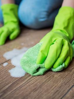 床を掃除するクローズアップのゴム手袋