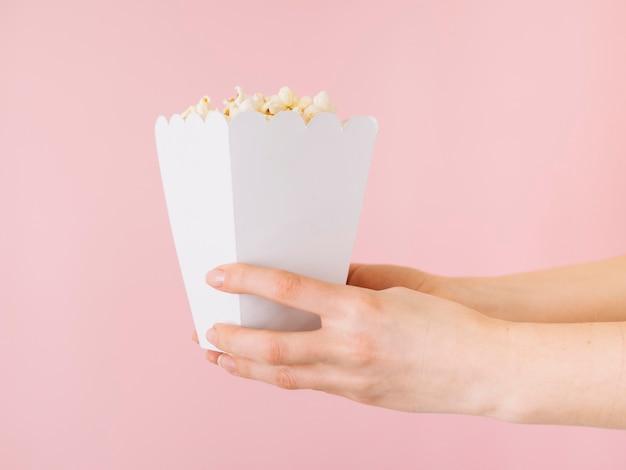 Руки крупного плана держа коробку попкорна
