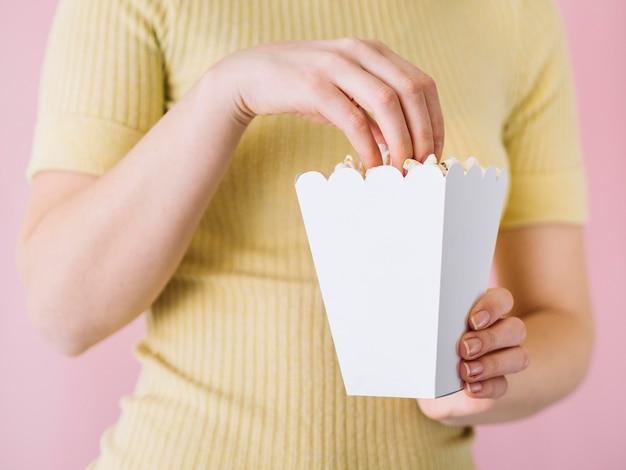 Крупным планом лицо, принимающее соленый попкорн