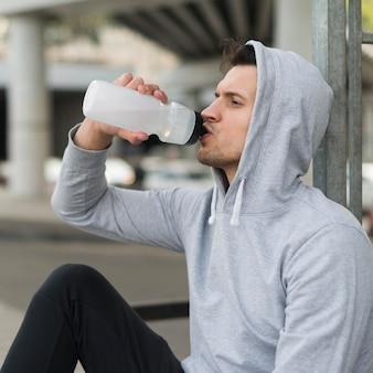 Взрослый мужчина пьет воду после тренировки