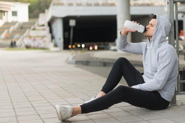 大人の男性は屋外の水を飲む
