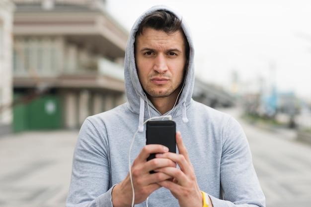 Портрет взрослого мужчины держит свой мобильный телефон