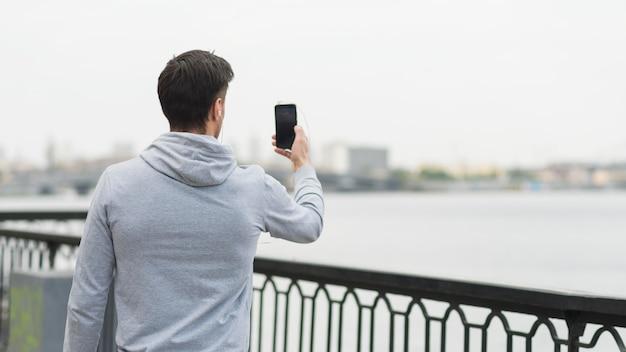写真を撮る背面図成人男性
