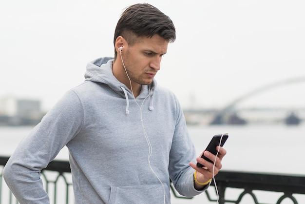 Спортивный взрослый мужчина просматривает свой мобильный телефон
