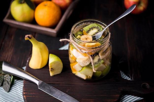 Баночка, наполненная здоровыми фруктами на столе
