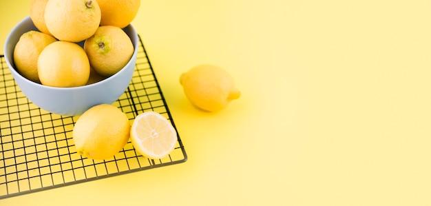 Органические лимоны в миску с копией пространства