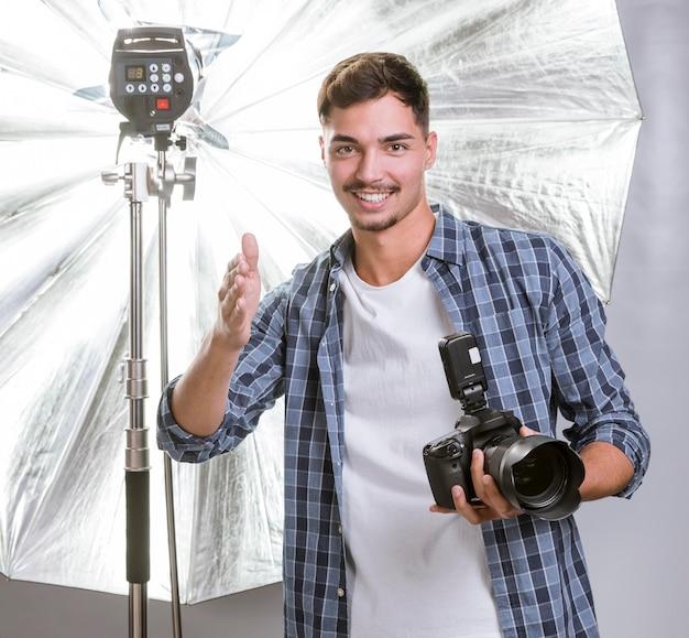 Вид спереди смайлик мужчина держит профессиональную камеру