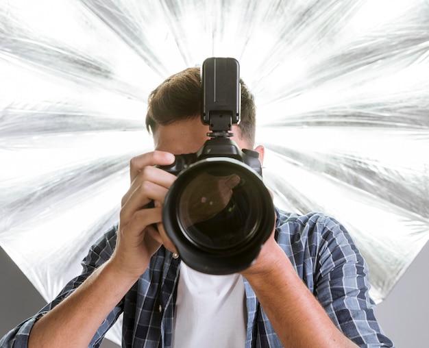 Фотограф мужчина держит профессиональную камеру