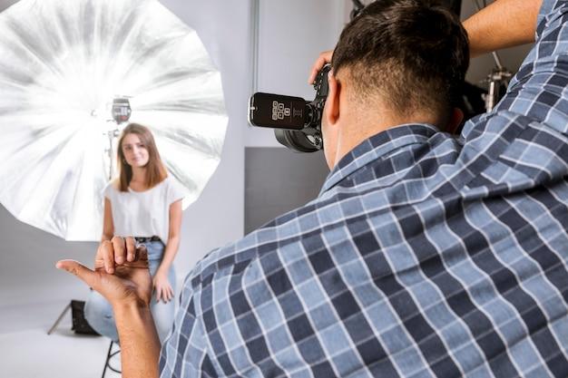 Человек берет фотографию женщины, сидящей на стуле
