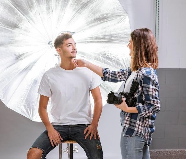 Женщина помогает мужчине позировать для фото