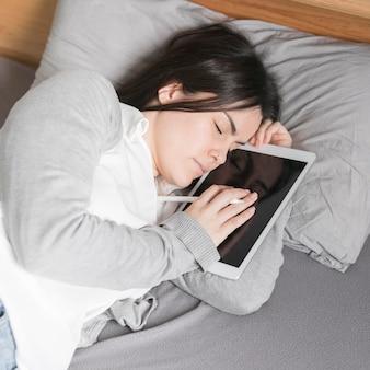 Женщина спит с планшетом