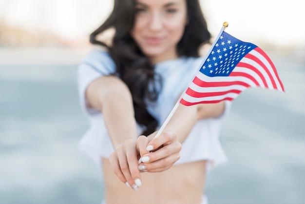 Крупным планом брюнетка женщина держит флаг сша