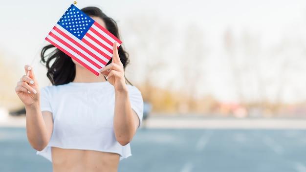 Середине выстрел женщина держит флаг сша над лицом