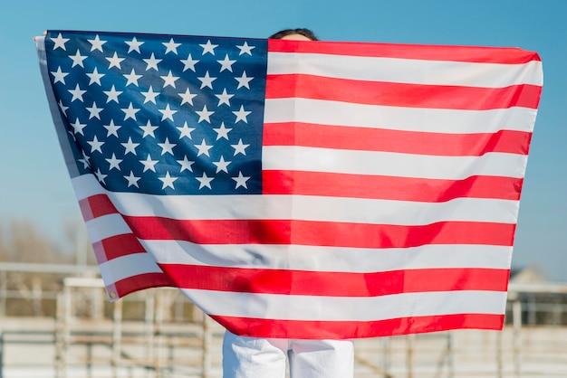 Женщина держит большой флаг сша над собой