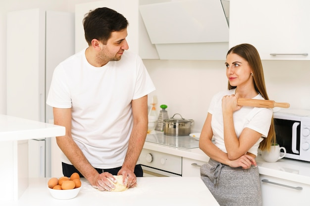 Молодая пара делает тесто вместе