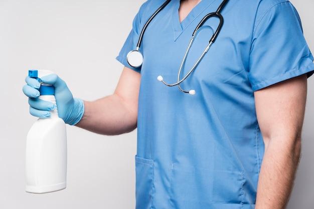 消毒剤とスプレーボトルを保持しているクローズアップの看護師