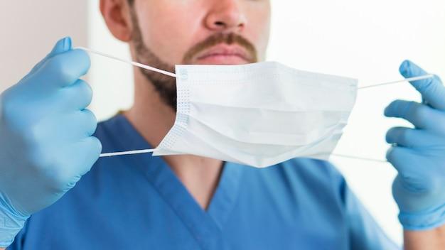 Крупным планом медсестра держит медицинскую маску