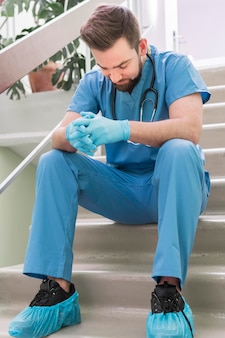 Крупным планом мужской медсестра, принимая перерыв на работе