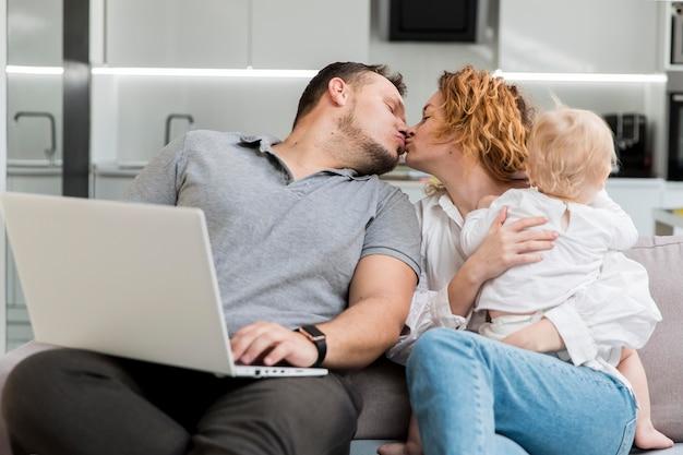 ミディアムショットの両親のキス