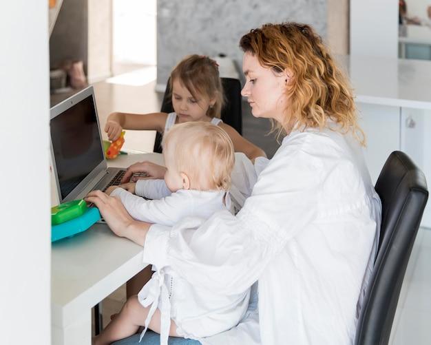赤ちゃんと一緒に働くサイドビュー母
