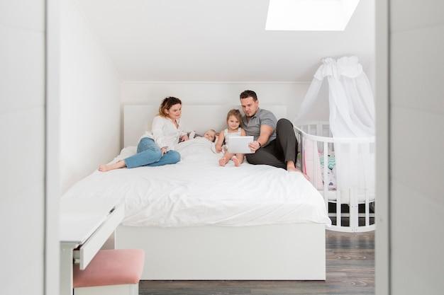 Семья лежит в постели с планшетом