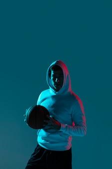 クールなライトで一人でバスケットボールをする人