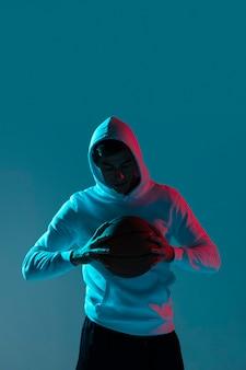 若い男がクールなライトだけでバスケットボールをプレー