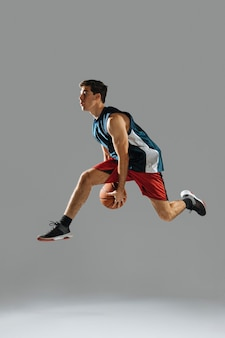 サイドビューの若い男がバスケットボールをしながらジャンプ