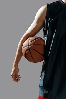 若い男が彼のバスケットボールを保持