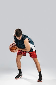 背の高い男が一人でバスケットボールをプレー
