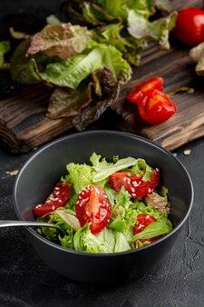 暗いボウルにトマトとハイアングルの新鮮なグリーンサラダ