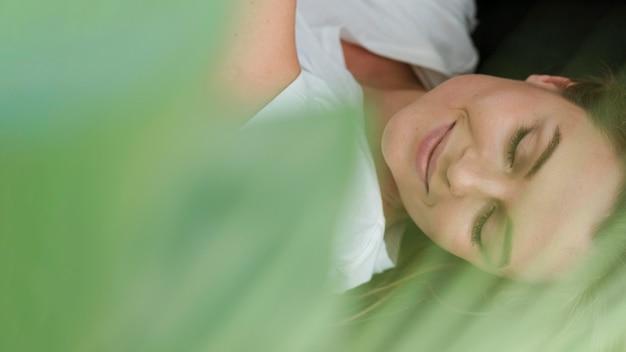 Крупным планом женщина с закрытыми глазами и размытым растением